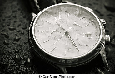 Unclear time - Wristwatch covered with rain drops
