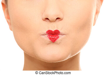 Valentine kiss - A close-up of female lips with a red heart...