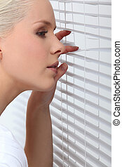Blond woman peering through window blind