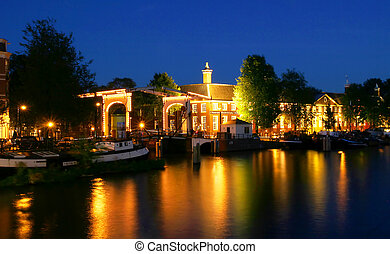 View on small bridge and illuminated houses on city canal (Amstel river) at evening in Amsterdam, Netherlands (Holland).