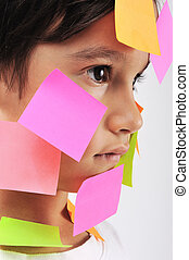 Little boy with memo notes on his face