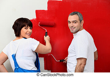 Married couple painting wall