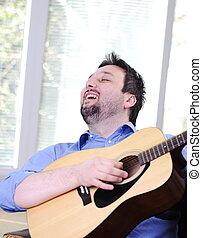 Man playing guitar and singing indoor at sofa