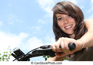 Young woman riding a bike in the summertime