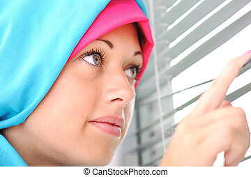 Muslim girl looks out of the window through a jalousie