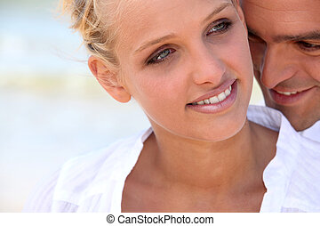 blonde woman hugged tenderly from the back by her partner