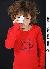 Young girl drying her tears