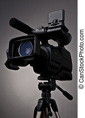 Camcorder - Video camera and tripod on gray background