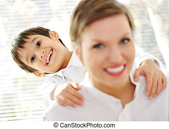 Portrait of young mother piggybacking her son indoor