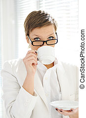 Young business woman drinking coffee at office