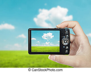 Hand holding digital camera and making landscape photograph
