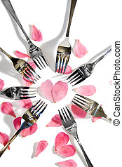 gold and silver forks surrounding heart shape with rose petals