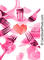 pink forks surrounding heart shape and rose petals