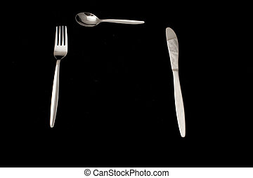Fork, knife and spoon on a black background