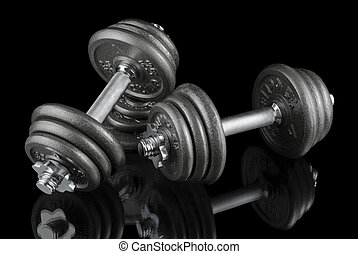 Two dumbbells on black - Low-key studio shot of two heavy...