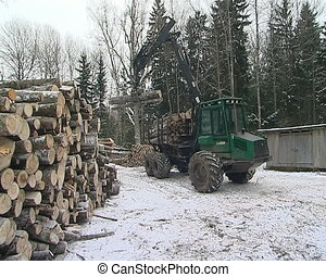 Special mashine with crane unload tree trunks from trailer