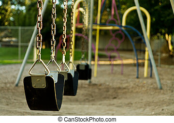 Empty childs swing set - Swing set at a playground that is...