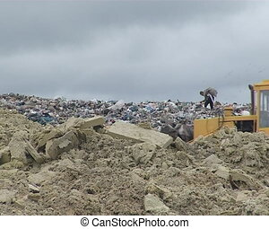 Dump. Machine weighs on garbage and homeless people.