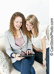 Two women using tablet computer - Two smiling women using...