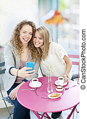 Woman showing phone to friend - Two smiling women looking at...