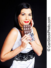 girl eating chocolate - pretty happy young brunette woman...