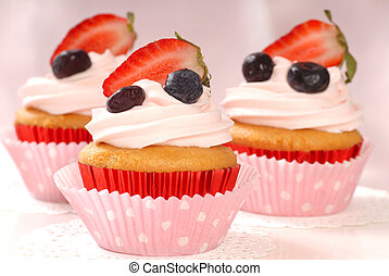 Delicious vanilla cupcake with strawberry frosting and fresh strawberries and blueberries