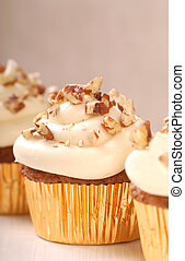 Delicious carrot cake cupcakes with cream cheese frosting and chopped pecan nuts