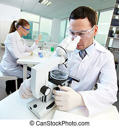 At the lab - Male researcher looking through the microscope,...