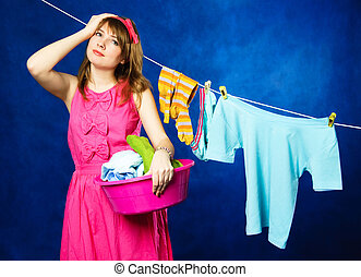 young housewife hanging clothes on clothesline - charming...