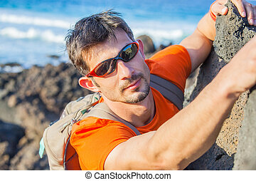 Young man in glasses with backpack climbing indoor wall....