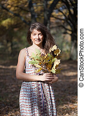 girl with oak leaves posy in autumn park - Outdoor portrait...