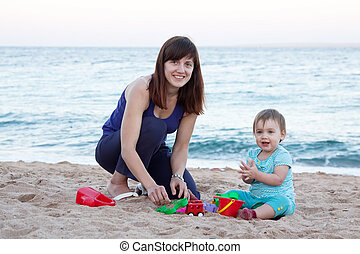 mother with  toddler plays on  beach