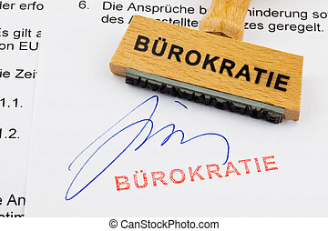 wooden stamp on the document: bureaucracy - a stamp made of...