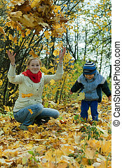mother with   boy throw up  leaves in autumn