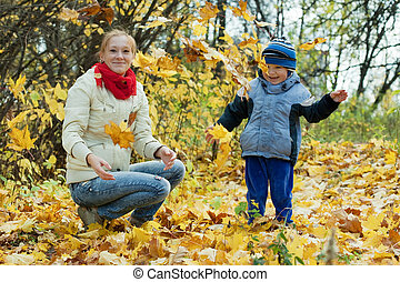 Happy mother with boy throw up maple leaves in autumn