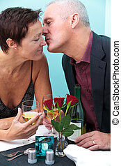 Mature couple restaurant kiss - Photo of a mature married...