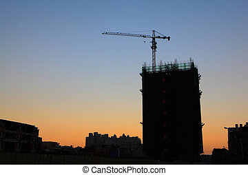 construction cranes silhouette with sunset