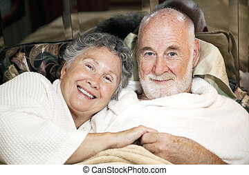Senior Couple in Bed - Portrait of loving senior couple in...