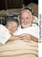Senior Couple Asleep - Senior couple asleep in bed, holding...