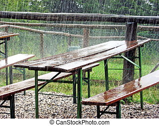 picnic tables for a feast abandoned during the shower