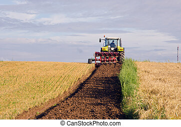 Tractor plow agricultural field harvested land