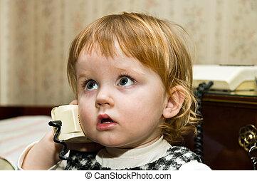 Cute little girl speaking retro telephon