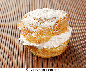 Single cream puff - A single cream puff on a bamboo placemat