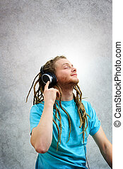 Portrait of a Young Man with Dreadlocks Listening to Music...