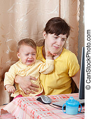 mother working with computer - mother with crying baby...