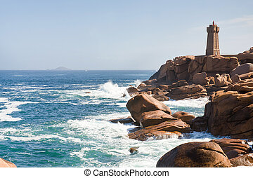 lighthouse in the rocks on Brittany Pink Granite Coast in...