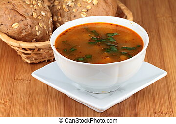 Goulash soup on white plate with cereal rolls