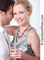 Man and woman in a clinch, dancing and drinking champagne