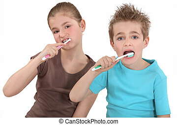 Brother and sister brushing their teeth.