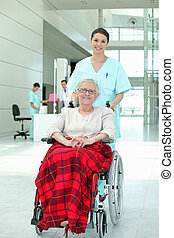 Hospital nurse pushing an elderly lady in a wheelchair